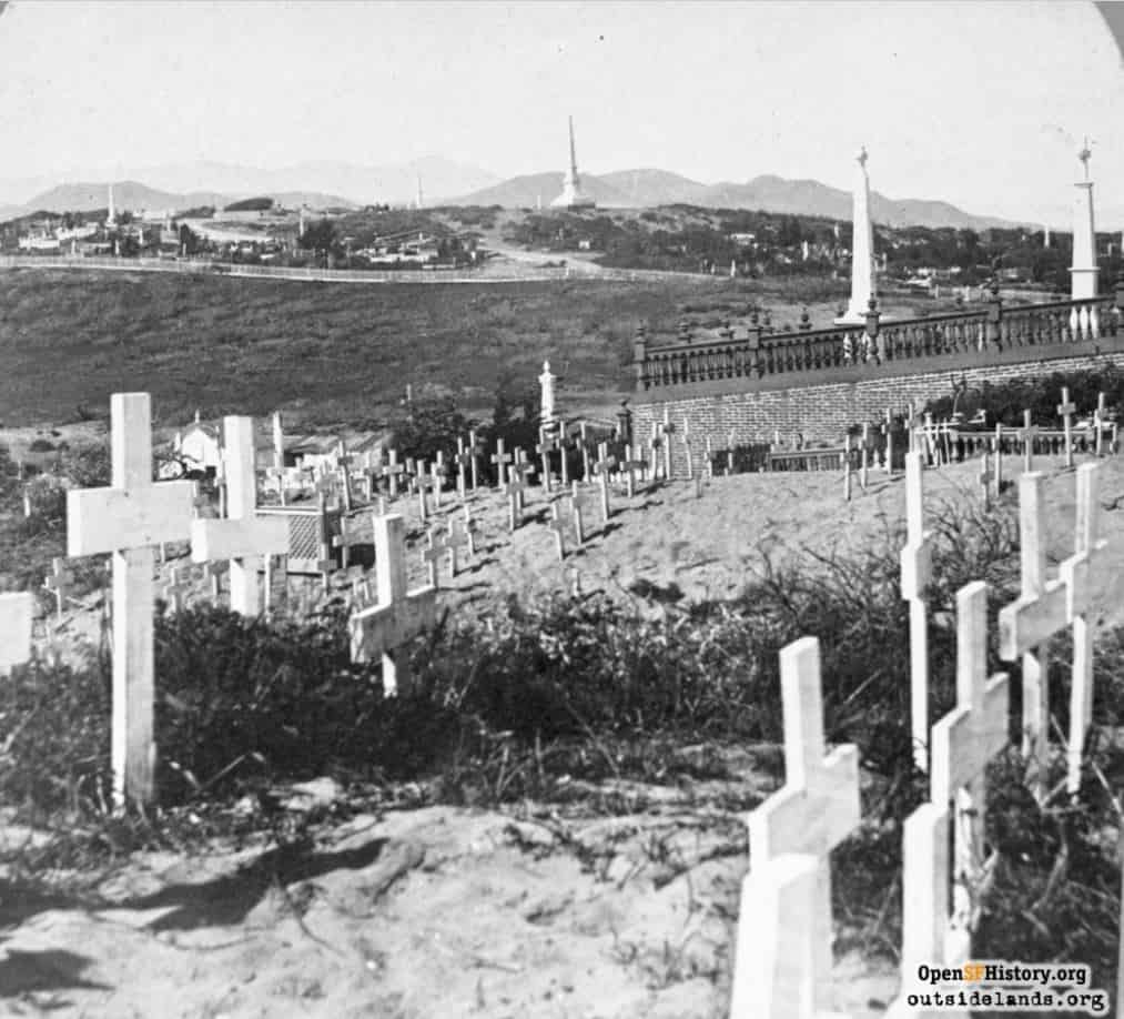 Looking north from Masonic Cemetery towards Odd Fellows on the western slope of Lone Mountain. Note the Marin Headlands and Mt. Tamalpais in the background. Also note the extreme sandy conditions of the area. Prior to the development and growth of San Francisco, wind swept sand and dunes were the predominant feature of the area. Sand proved a very unstable soil for wood crosses, headstones, and monuments. It also took copious amounts of water to maintain the large 'green' landscaped grounds.