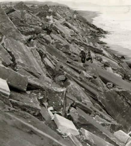 People climbing over the remains of San Francisco's cemeteries dumped along Ocean Beach